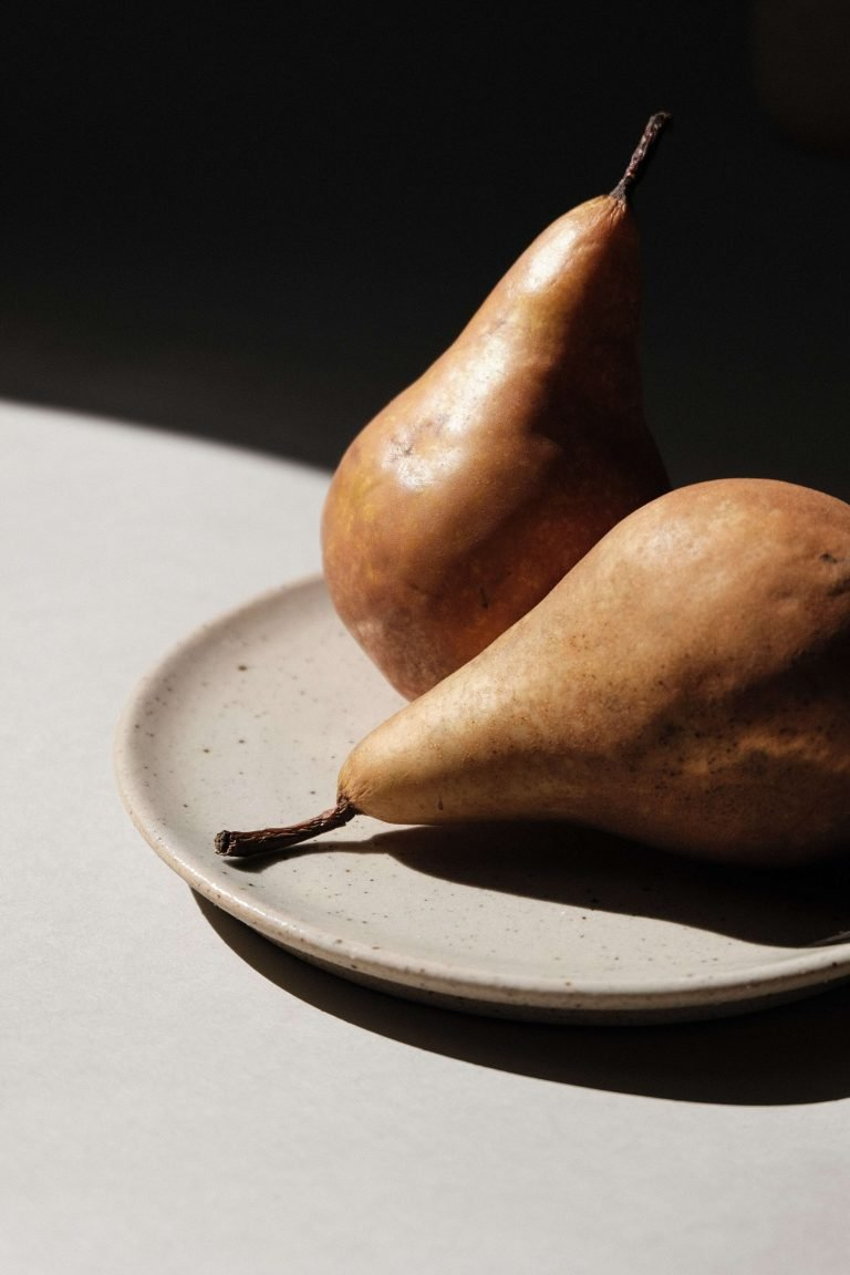 Pears on a plate with dark shadow. Find Your Feel Nutrition