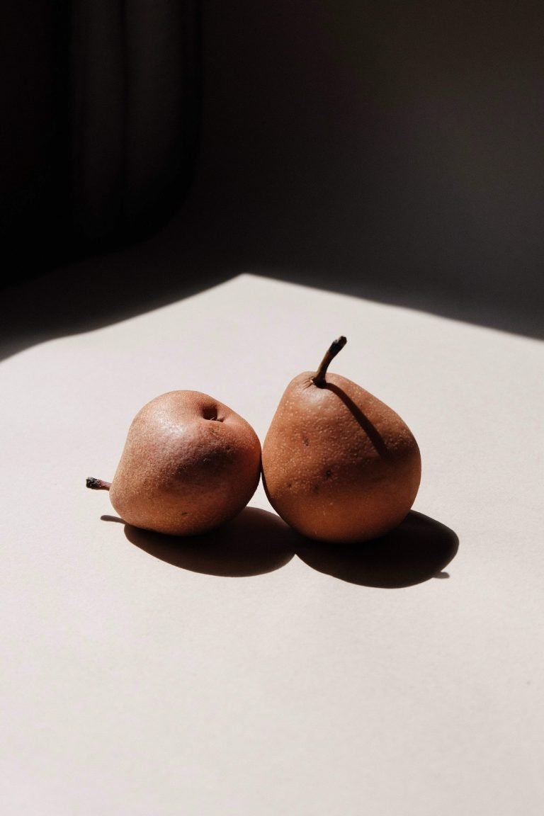 red pears on a white table with a dark black background