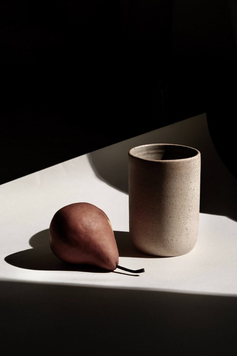 single red pear next to a ceramic mug on white paper with a dark background. Find Your Feel Nutrition